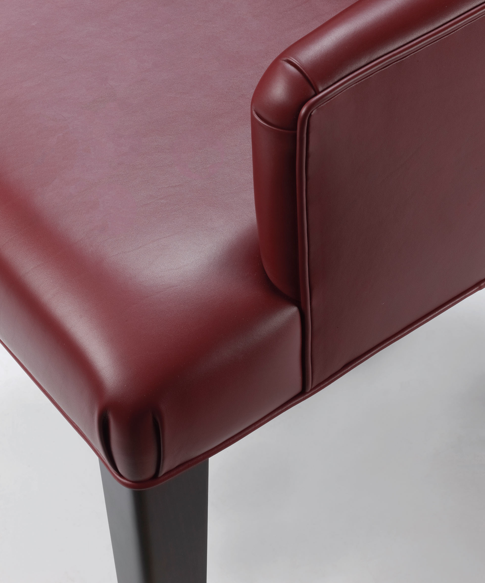 Detail of the bronze handle on the back of Isotta, a wooden dining chair with or without armrests and with a fabric or leather covered back, from Promemoria's catalogue   Promemoria
